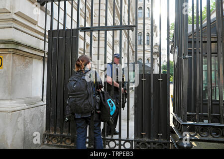 A female photographer waiting for permission to pass through the Downing Street gates City of Westminster, Central London England UK  KATHY DEWITT - Stock Photo