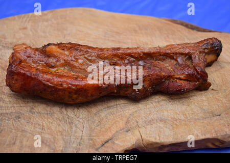Crispy cooked seasoned pork ribs on an olive wood chopping board - Stock Photo