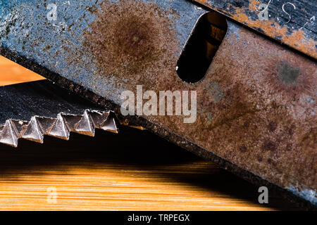 A Macro image of A very old, dull and rusty razor with an equally dirty and used serrated blade. - Stock Photo