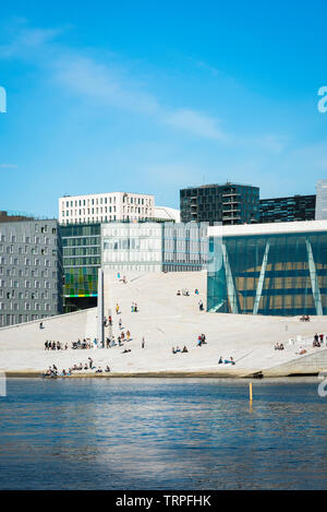 Oslo Opera House, view across the fjord of people on the vast access ramp leading to the roof of the Oslo Opera House, with Barcode Buildings beyond. - Stock Photo