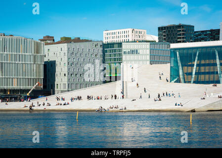 Opera House Oslo, view across the fjord of people on the vast access ramp leading to the roof of the Oslo Opera House, with Barcode Buildings beyond. - Stock Photo