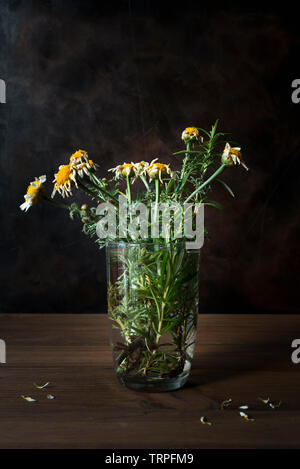 Concept of death. Still life with withered flowers in a glass with water on wooden table with dark background. - Stock Photo