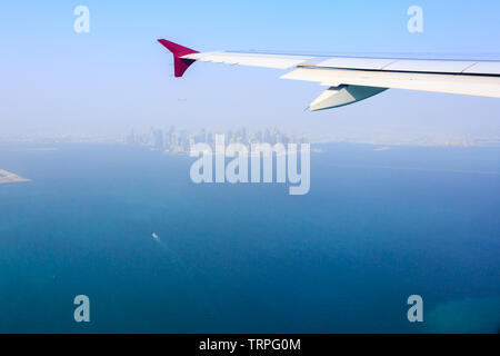 View of the city of Doha, Qatar from the airplane porthole. Plane flies over the skyscrapers. Travel concept. - Stock Photo