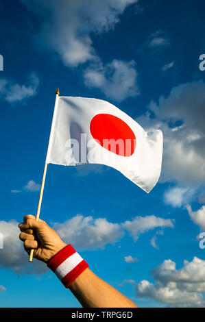 Hand with Japan red and white wristband holding a Japanese flag waving in bright sunny blue sky - Stock Photo