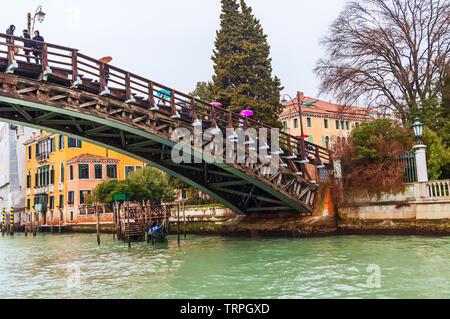 Venice on a rainy day when people are crossing Grand Canal through an over-bridge with colorful umbrellas - Stock Photo