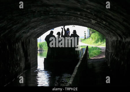 Silhouetted rear view of people in UK narrowboat on British canal moving through dark tunnel; upside down man, legs in air, propels boat by legging. - Stock Photo