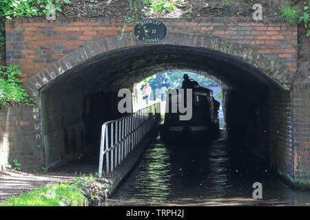 Silhouetted rear view of narrowboat on a UK canal moving away through a dark canal tunnel; people on towpath watching at other end in bright sunlight. - Stock Photo