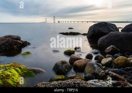 The East Bridge of the Great Belt Bridge from the Granskoven strand in Denmark with colorful rocks and the sea in the foreground - Stock Photo