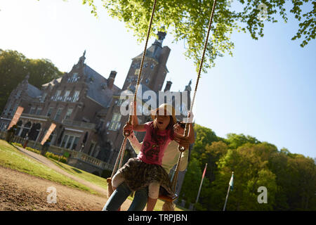 Asian mother and her young daughter having fun playing on a swing hanging on a large tree in front of a castle in bright summer sunshine - Stock Photo