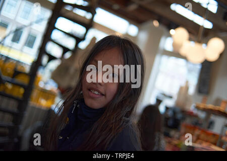 Portrait of a happy looking teenage Asian girl inside a restaurant in bright daylight - Stock Photo