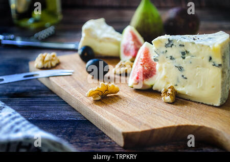 Blue cheese and Camambert with figs on wooden board - Stock Photo