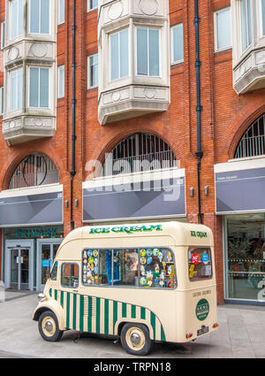 A cute, retro designed, green and cream ice cream van, parked outside shops in Ealing Broadway shopping centre. Ealing, London W5, England, UK. - Stock Photo