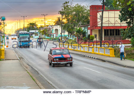 A red LADA car driving in the morning. There is a dramatic-sky sunrise in the Central Road which traverse the city from one point to the other. There - Stock Photo