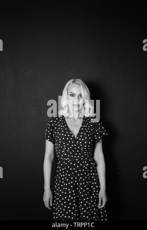 Studio portrait of beautiful blonde woman in a black dress against black plain background - Stock Photo