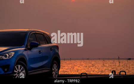Blue compact SUV car with sport and modern design parked on concrete road by the sea at sunset in the evening. Hybrid and electric car technology - Stock Photo