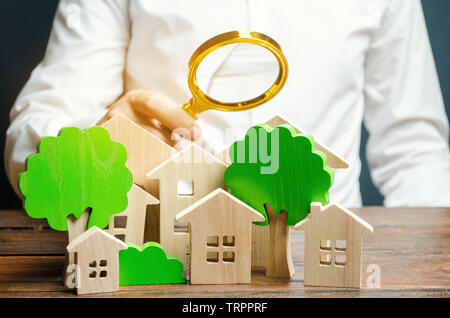 A man holds a magnifying glass over wooden houses and trees. Real estate valuation and selection of a place for the construction of new buildings. Eva - Stock Photo