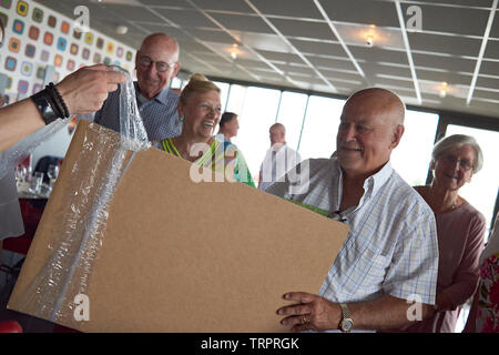 A group of elderly retired friends celebrating a 50th wedding anniversary at a restaurant with the happy couple unwrapping presents - Stock Photo