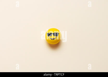 Smiling emoticon ball with sunglasses on pastel background - Stock Photo