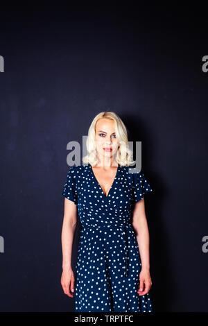 Studio portrait of beautiful blonde woman in a dark blue dress against black plain background - Stock Photo
