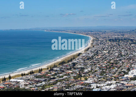 View of Tauranga from Mount Maunganui in New Zealand. The surf rolls on to the perfect sandy beach - Stock Photo