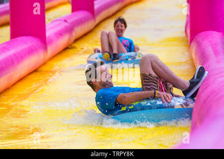 Man and woman sitting on inflatable rings having fun on giant waterslide, water slide, at Bournemouth, Dorset UK in June - Stock Photo