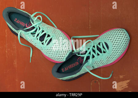 Pair of Perfect Asics NOOSA FF 2 shoes in pale blue and pink colours for running on terracotta background. Moscow - June 2019. Shoes for longer races - Stock Photo
