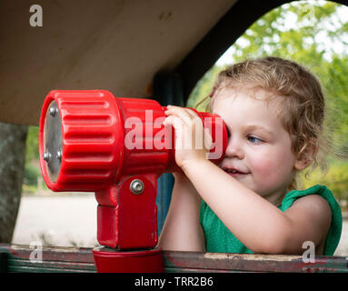 Young girl looking through telescope in playground - Stock Photo