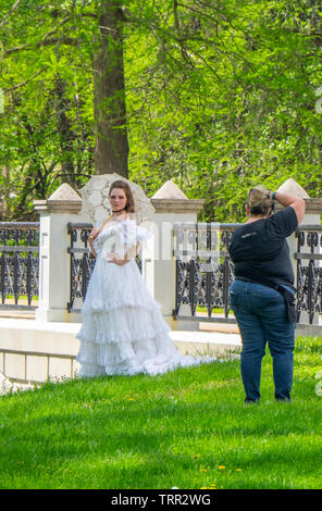 Woman in white lace dress posing for photograph in Forest Park St Louis Missouri USA. - Stock Photo