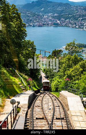 Monte Bre, Switzerland - June 08, 2019 View of the Mont Bre funicular going down with lake Lugano at the background - Stock Photo