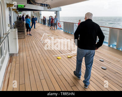 Passengers playing Shuffleboard on the deck of the TUI cruise ship Marella Explorer, North Sea, Europe - Stock Photo