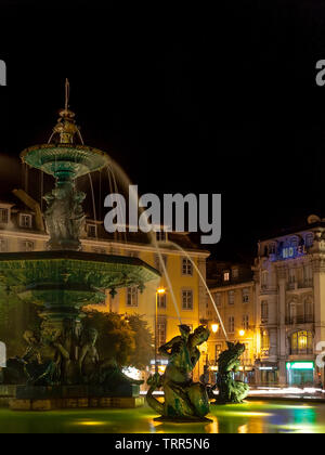 Lisbon, Portugal. Fountain in Dom Pedro IV Square aka Rossio by night with mermaids and mythological creatures. 19th century Val d'Osne Foundry work. - Stock Photo