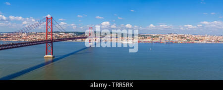 Lisbon, Portugal. Ponte 25 de Abril Suspension Bridge with Lisbon in background. Connects the cities of Lisbon and Almada over the Tagus River. - Stock Photo
