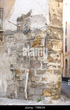 Detail of the corner of an old stone house with wiring and oldness of signboard in Palermo, Italy. Text: 'Welding work Electric and gas welding..' - Stock Photo
