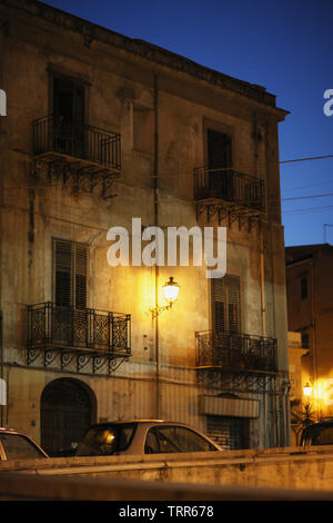 Facade of old racy houses with balconies and a lantern in the night sky in Palermo, Italy. - Stock Photo