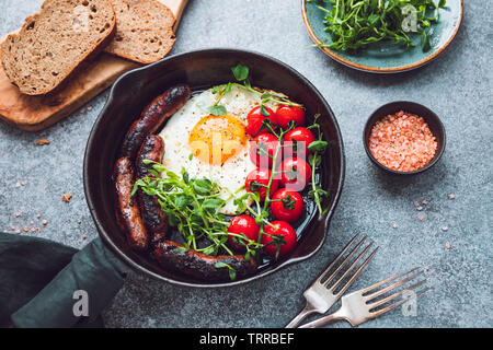 Breakfast time, fried egg with sausages and cherry tomatoes in a black iron pan, served microgreens. - Stock Photo