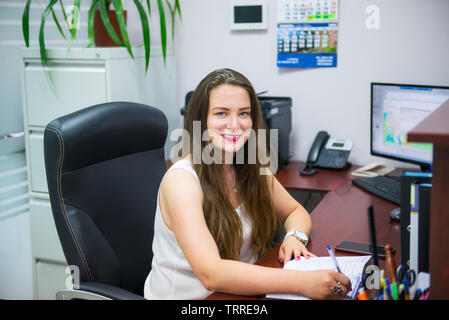 Young caucasian business lady is looking at camera and smiling while sitting on her workplace in office. Female entrepreneurship. Portrait of skilled - Stock Photo