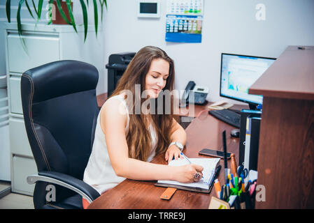 Young caucasian business lady sitting on her workplace in office. Female entrepreneurship. Portrait of skilled manager satisfied with occupation. Sele - Stock Photo