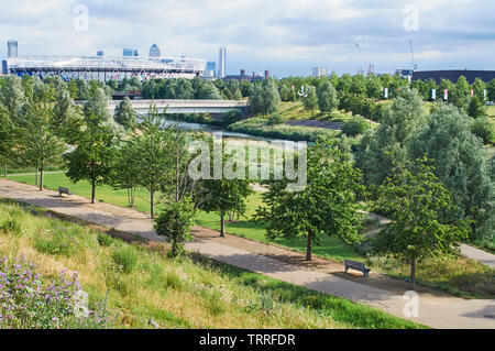 The Northern Parklands in London's Olympic Park in early summer, looking towards the London Stadium, with Canary Wharf in the far distance - Stock Photo