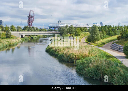 The Northern Parklands in London Olympic Park, looking along the River Lea towards the London Stadium and the ArcelorMittal Orbit - Stock Photo