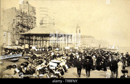An early twentieth century picture postcard of Hastings Promenade, East Sussex, England, showing a bandstand and a crowd as audience. - Stock Photo