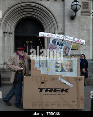 London, UK. 11th June 2019. Protester on no 1 Parliament Street, London, UK, with a collage of newspaper articles depicting Boris Johnson, once of the candidates for the job of Prime Minister of the UK, asking the question 'would you trust this man with a piggy bank'. Credit: Joe Kuis / Alamy News - Stock Photo