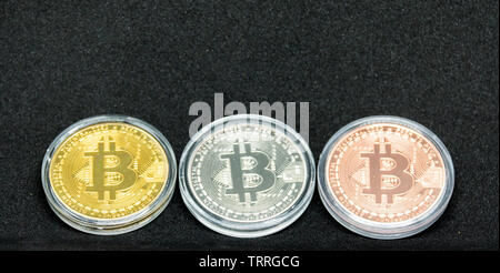 Gold, silver and bronze bitcoin coins in a protective case. - Stock Photo