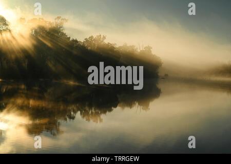 The early morning sun lights up river-fog on the Murray River near Mildura, Australia. - Stock Photo