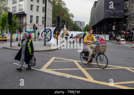London, England, UK - April 23, 2019: A cyclist rides past a protest camp by Extinction Rebellion at Marble Arch in central London. - Stock Photo