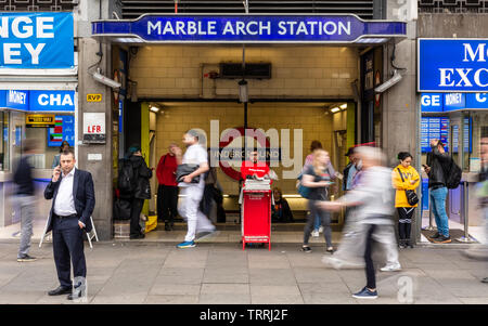 London, England, UK - April 23, 2019: Crowds of commuters walk past the entrance to Marble Arch tube station at rush hour on London's Oxford Street. - Stock Photo