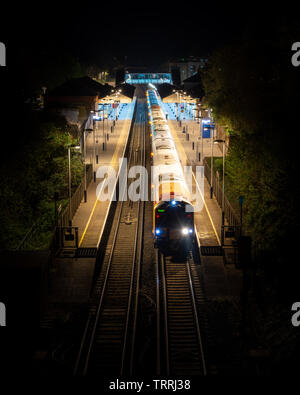 Winchester, England, UK - April 22, 2019: A South Western Railway passenger train calls at Winchester Railway Station in Hampshire at night. - Stock Photo