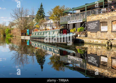 London, England, UK - March 24, 2019: A traditional narrowboat is moored on the Grand Union Canal beside Grand Junction Arms pub in North Acton. - Stock Photo