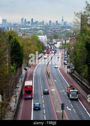 London, England, UK - April 13, 2011: Traffic flows along the Archway Road in the North London suburbs, with the skyline of the City of London busines - Stock Photo