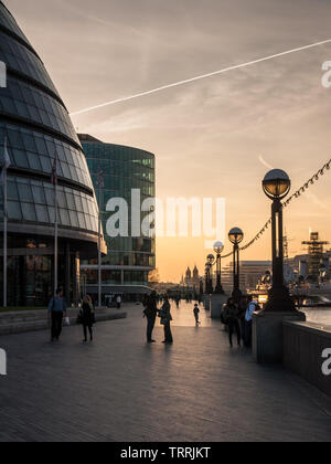 London, England, UK - April 23, 2010: People walk along the River Thames Path outside London City Hall at sunset. - Stock Photo