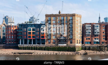London, England, UK - April 15, 2010: Sun shines on apartment buildings and office blocks on the side of the River Thames in the City of London. - Stock Photo